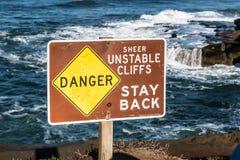 Niebezpieczeństwo znak z oceanu tłem przy zmierzch falezami Zdjęcie Stock