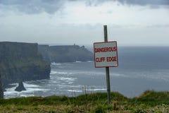 Niebezpieczna falezy krawędź podpisuje wewnątrz chmurzącą pogodę przy falezami Moher w Irlandia Niebezpieczeństwa szyldowy ostrze Zdjęcie Stock