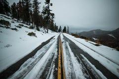 Niebezpieczna uncleared śliska asfaltowa zimy droga z śniegiem w górach Obraz Royalty Free