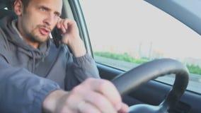 niebezpieczne kierowanie Mężczyzna jeżdżenie, przysięga na jego telefonie komórkowym Boczny widok zdjęcie wideo