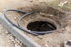 Niebezpieczny nieosłonięty manhole na ulicie bez barier Naruszenie bezpieczeństwo rządzi podczas naprawy miastowy i budowy zdjęcia stock