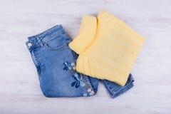 Niebiescy dżinsy i żółty pulower na białym drewnianym tle Kobiety ` s moda odziewa Zdjęcia Stock