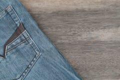 Niebiescy dżinsy na brown drewnianym tle Zdjęcie Royalty Free