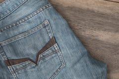 Niebiescy dżinsy na brown drewnianym tle Zdjęcie Stock