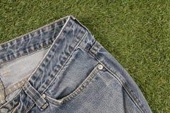 Niebiescy dżinsy na Sztucznym trawy tle Obrazy Royalty Free