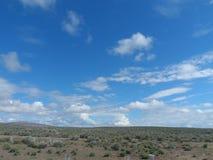 Niebieskie niebo bawi się few bufiaste chmury na słonecznym dniu zdjęcie stock