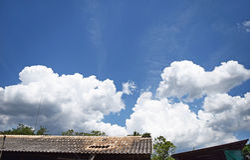 Niebieskie niebo bielu chmury housetop i tło fotografia royalty free