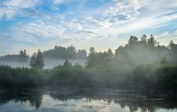 Niebieskie niebo i mgłowy jeziorny las fotografia stock