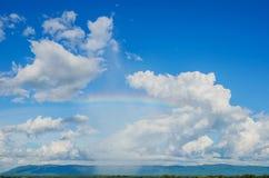 Niebieskie niebo i tęcza na górze Obraz Royalty Free
