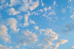 Niebieskie niebo krajobraz z białymi dramatycznymi chmurami zaświecał evening światło słoneczne Zdjęcie Stock