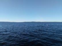 Niebieskie niebo nad jeziorem, morzem falistymi/ fotografia stock