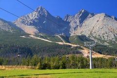 Niebieskie niebo nad pogodnym Lomnicky szczytem, narciarskimi skłonami i wagonami kolei linowej, Fotografia Stock