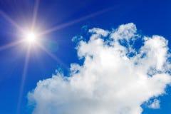 Niebieskie niebo z chmurami i jaskrawym słońcem z promieniami obraz royalty free