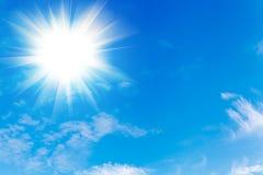 Niebieskie niebo z chmurami i jaskrawym słońcem z promieniami zdjęcie stock