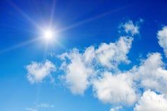 Niebieskie niebo z chmurami i jaskrawym słońcem z promieniami zdjęcia stock