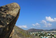 Niebieskie niebo z skałami i miastem Obrazy Stock