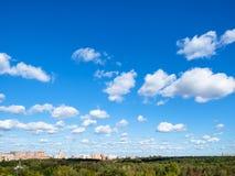 Niebieskie niebo z wiele biel chmurami nad drewnem i miastem obraz stock