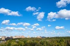 Niebieskie niebo z wiele biel chmurami nad parkiem i miastem zdjęcie royalty free