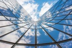 Niebieskiego nieba i bielu chmury odbija w szklanym budynku zdjęcia stock