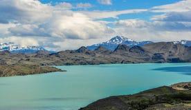 Niebieskozielony jezioro z górami w tle obrazy stock