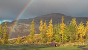 Niebla anaranjada fría de la mañana del otoño con el arco iris y la tienda en las montañas metrajes