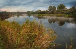 Niebla del amanecer del otoño por mañana nublada en el río Fotos de archivo libres de regalías