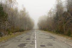 Niebla en el camino de la montaña Fotos de archivo