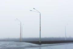 Niebla en el camino solo Luces de calle, brumoso de niebla, linternas de los posts de la lámpara, camino abandonado en la niebla  Imagen de archivo libre de regalías