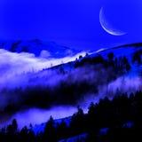 Niebla en un valle con las montañas y la luna Fotografía de archivo libre de regalías