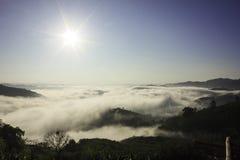 Niebla, sol, cielo y montaña Foto de archivo