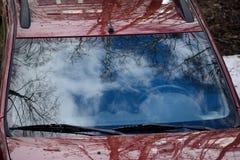 Niebo chmura i drzewa odbijający w przedniej szybie samochód karmazyny barwimy fotografia royalty free