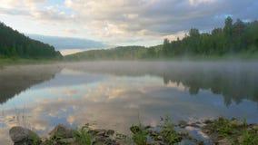 Niebo z chmurami odbija w szerokim jeziorze z rozpraszać mgłę zbiory wideo