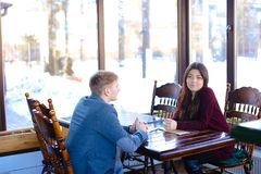 Niece meet with uncle in cafe to discuss present for mother stock photos
