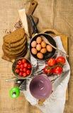 Niecka pełno jajka, pokrojony chleb, ser, pomidory, dwa filiżanki, knifes, grater na białym papierze i kanwa, Fotografia Stock