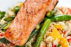 Niecka smażył łososia z czułym asparagusem i courgette słuzyć na couscous mieszającym z słodkim pomidorem, koloru żółtego pieprzo obrazy royalty free