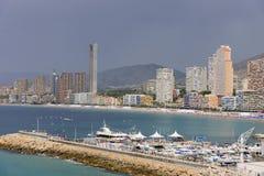 Niecka widok Benidorm Poniente plaża z portem, drapaczami chmur, łodziami i górami w Benidorm, Alicante, Hiszpania z podeszczowym obrazy royalty free