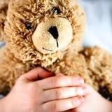 niedźwiadkowy dziecko wręcza starego miś pluszowy Zdjęcia Royalty Free