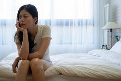 Niedergedrückte Frau auf Bett betrachten über Probleme stockfoto