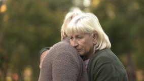 Niedergedrückte reife Frauen, die umarmen, um sich, Familienprobleme, Sorgfalt zu stützen stockbilder