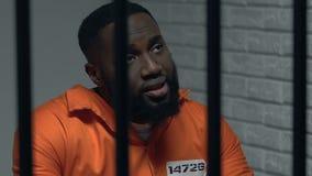 Niedergedrückter afro-amerikanischer Gefangener, der über gemachtes Verbrechen, Lebenfehler bedauert stock video