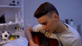 Niedergedrückter nachdenklicher Jugendlicher, der Gitarre im Schlafzimmer, leidendes erstes Auseinanderbrechen spielt lizenzfreie stockfotografie
