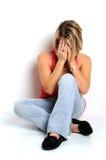 Niedergeschlagene Frau, die auf Fußboden sitzt Stockfotografie