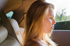 Niedergeschlagene Frau, die in einem Auto sitzt Lizenzfreies Stockfoto