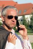 Niedergeschlagener Geschäftsmann unter Verwendung des Handys Stockbild