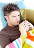 Niedergeschlagener junger Mann, der auf der Couch mit Tee liegt Stockfotos