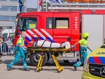 Niederländische Feuerwehrmänner und ärztliche Bemühungen in der Aktion Stockbild