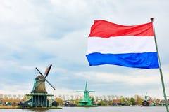 Niederländische Flagge und Windmühle auf Kanal Stockfotos