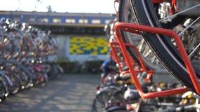 Niederländische Frau, die ihr Fahrrad am Parken für Fahrräder in zwei Niveaus an Eindhoven-Hauptleitung Bahnhof zuschließt europa stock video