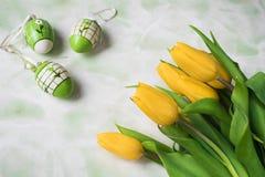 Niederländische gelbe Tulpen mit dekorativen weißen grünen Eiern lizenzfreie stockbilder