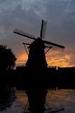 Niederländische Mühle durch Sonnenuntergang an einem See Lizenzfreie Stockfotografie
